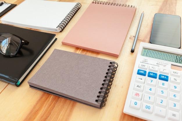 Bloco de notas com caneta e calculadora em cima da mesa.