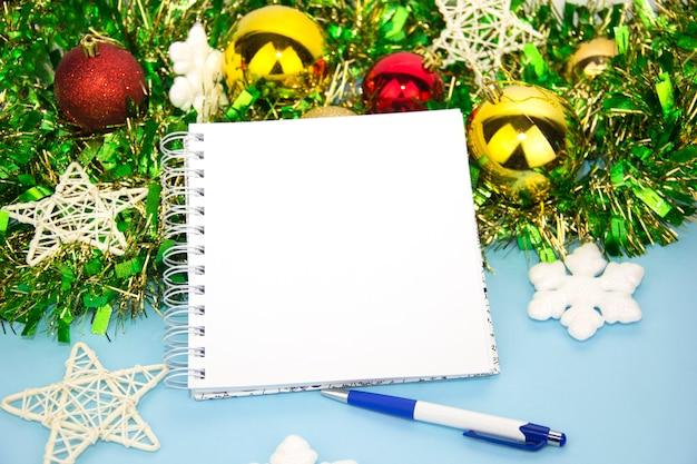 Bloco de notas com caneta e enfeites de natal. fundo azul de ano novo. espaço para texto. antecedentes do novo ano. natal. noel. limpar bloco de notas aberto, presentes de natal