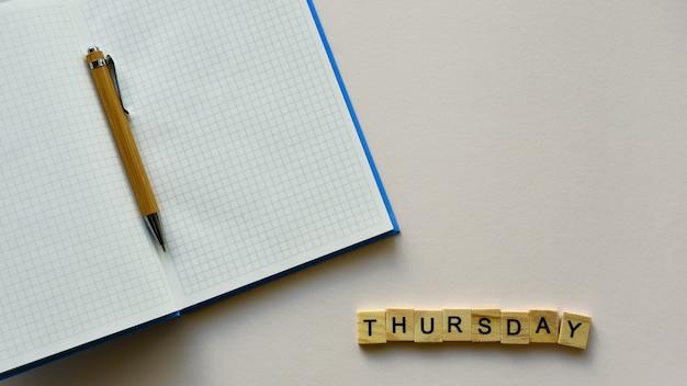 Bloco de notas com caneta e palavra de madeira