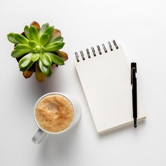Bloco de notas com caneta perto de caneca de café