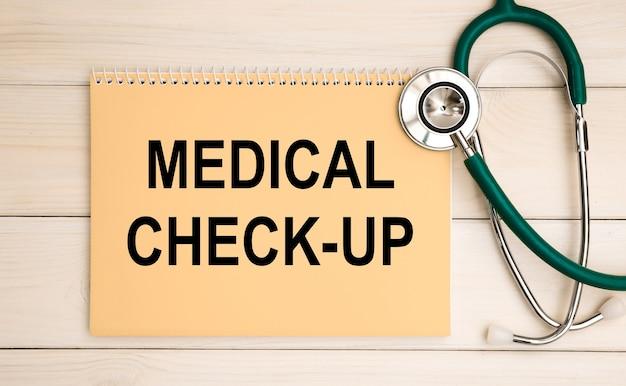 Bloco de notas com check-up médico de texto e estetoscópio. conceito médico.