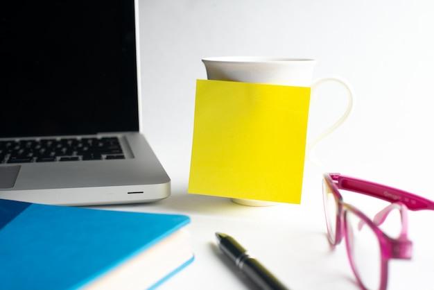 Bloco de notas com copo, copos com notebook e laptop