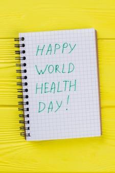 Bloco de notas com desejo feliz dia mundial da saúde. fundo amarelo mesa de madeira.