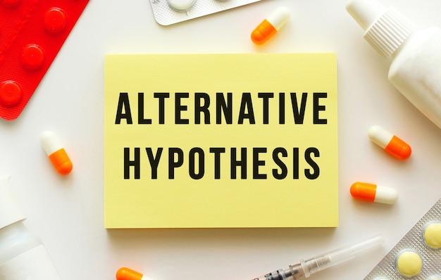 Bloco de notas com hipótese alternativa de texto em um fundo branco. nas proximidades existem vários medicamentos. conceito médico.