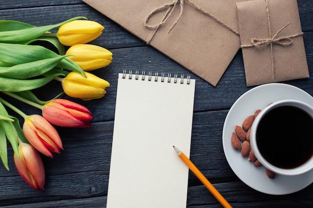 Bloco de notas com lápis ao lado das tulipas, café e envelopes.