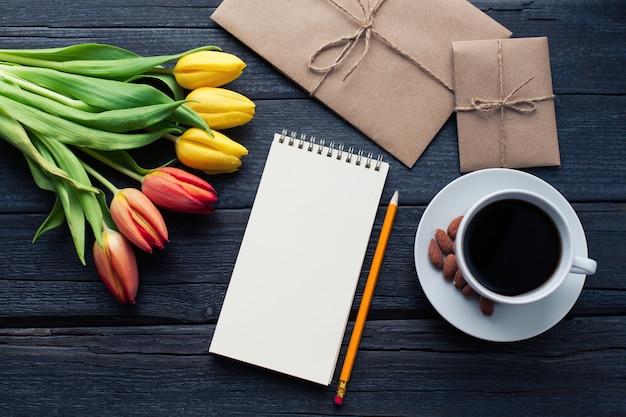 Bloco de notas com lápis ao lado das tulipas.
