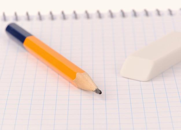Bloco de notas com lápis e borracha isolado sobre fundo branco