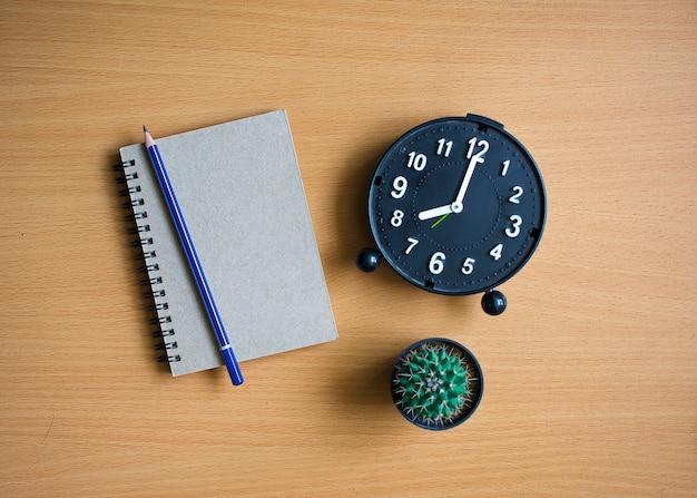 Bloco de notas com lápis e cacto no fundo da placa de madeira