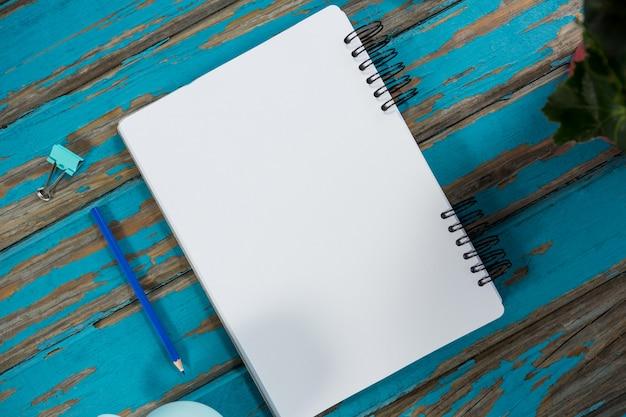 Bloco de notas com lápis e clipe de papel na mesa de madeira