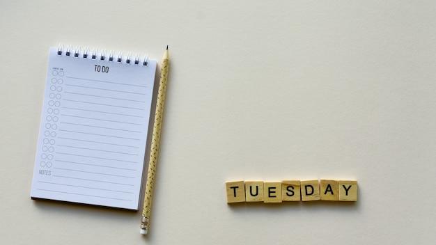 Bloco de notas com lápis e palavra de madeira