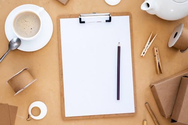 Bloco de notas com lápis e papel, xícara de café, composição de materiais e objetos feitos à mão. vista do topo