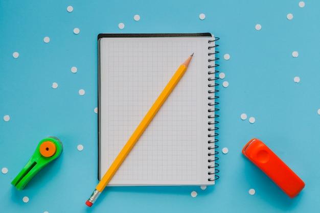 Bloco de notas com lápis e perfurador