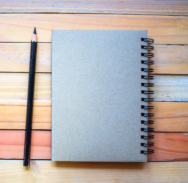Bloco de notas com lápis na placa de madeira background.using papel de parede para a educação