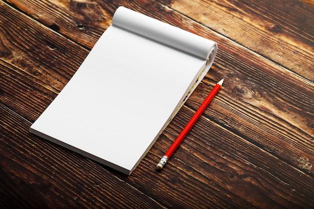 Bloco de notas com lápis vermelho sobre um fundo de mesa de madeira marrom, para educação, escrever metas e ações