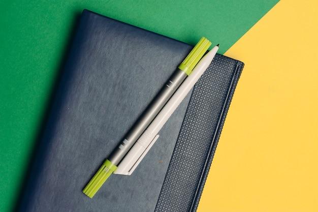 Bloco de notas com marcadores e canetas em fundo verde amarelo e espaço de código de material de escritório