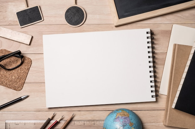 Bloco de notas com material escolar, globo, caderno e quadro-negro em uma mesa de madeira.