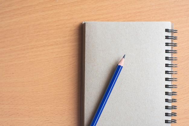 Bloco de notas com o lápis no fundo da placa de madeira. usando papel de parede para educação, foto de negócios. anote o produto para o livro com espaço de papel e conceito, objeto ou cópia.