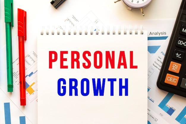 Bloco de notas com o texto crescimento pessoal em cartolina financeira colorida. caneta, calculadora na mesa do escritório.