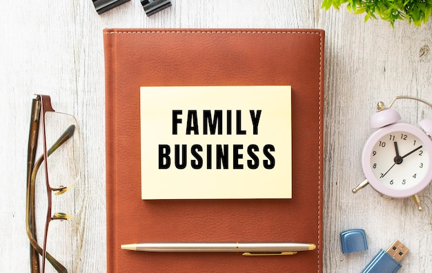 Bloco de notas com o texto empresa familiar em uma mesa de madeira. diário e caneta marrons. conceito de negócios.