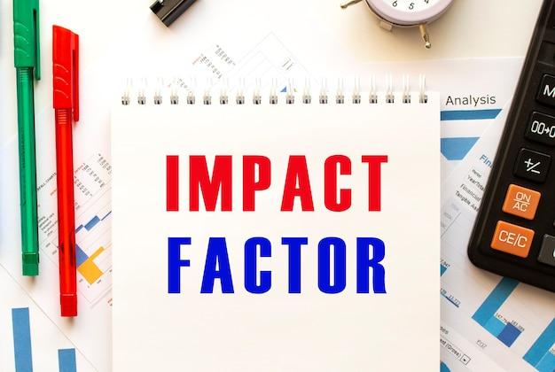 Bloco de notas com o texto factor de impacto na ficha financeira a cores. caneta, calculadora na mesa