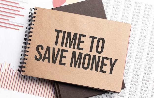 Bloco de notas com o texto hora de economizar dinheiro em gráficos e números. conceito de negócios.