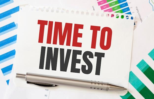 Bloco de notas com o texto hora de investir, clipes de papel, caneta, em diagramas financeiros. o negócio