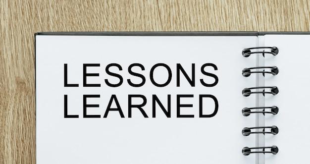 Bloco de notas com o texto lições aprendidas na mesa de madeira. conceito de negócios e finanças