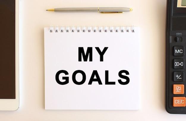 Bloco de notas com o texto meus objetivos em um fundo branco, perto de calculadora, tablet e caneta. conceito de negócios.