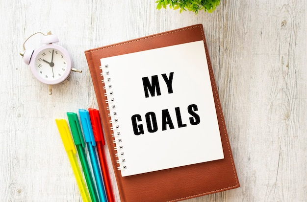 Bloco de notas com o texto meus objetivos sobre uma mesa de madeira. diário e canetas marrons. conceito de negócios.