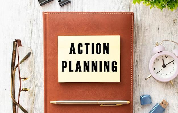 Bloco de notas com o texto planejamento de ações sobre uma mesa de madeira. diário e caneta marrons. conceito de negócios.