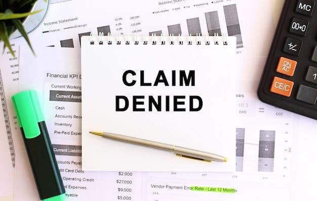 Bloco de notas com o texto reclamação negada em uma mesa branca, perto da calculadora e do material de escritório. conceito de negócios.