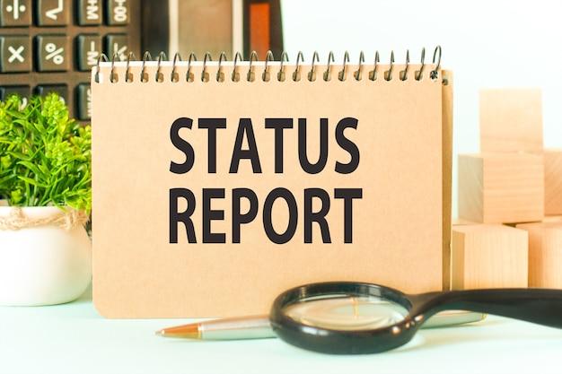 Bloco de notas com o texto status report folha de papel branco para notas, calculadora, lupa, blocos de woden, na parede de gráficos. conceito de negócios.