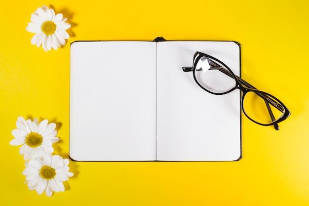 Bloco de notas com óculos e flores brancas