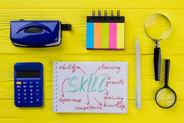 Bloco de notas com palavras de habilidade e artigos de papelaria. vista superior plana. mesa de madeira amarela.