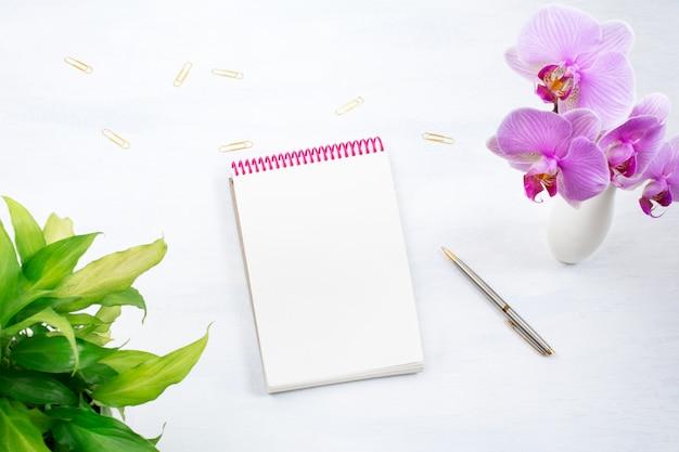 Bloco de notas com planta verde e flor de orquídea rosa