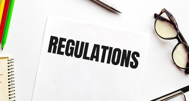 Bloco de notas com regulamentos de texto, em gráficos de negócios e caneta e gráficos