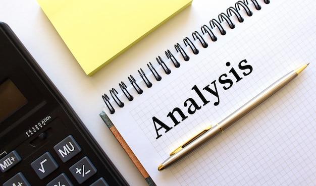 Bloco de notas com texto análise, ao lado encontra-se uma calculadora e papéis amarelos. conceito de negócios.