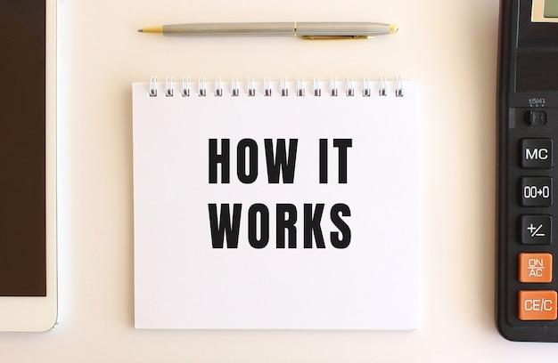 Bloco de notas com texto como funciona em um fundo branco, perto de calculadora, tablet e caneta.