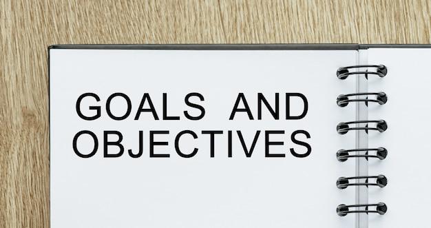 Bloco de notas com texto de metas e objetivos na mesa de madeira. conceito de negócios e finanças