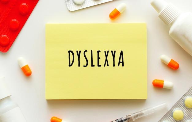 Bloco de notas com texto dislexya em uma mesa branca. nas proximidades existem vários medicamentos.