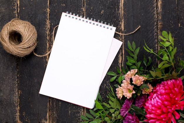 Bloco de notas com um buquê de flores em uma madeira escura vintage