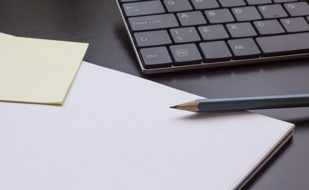 Bloco de notas com um lápis na mesa ao lado do teclado, close-up
