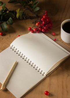 Bloco de notas com um ramo de rowan e uma xícara de café