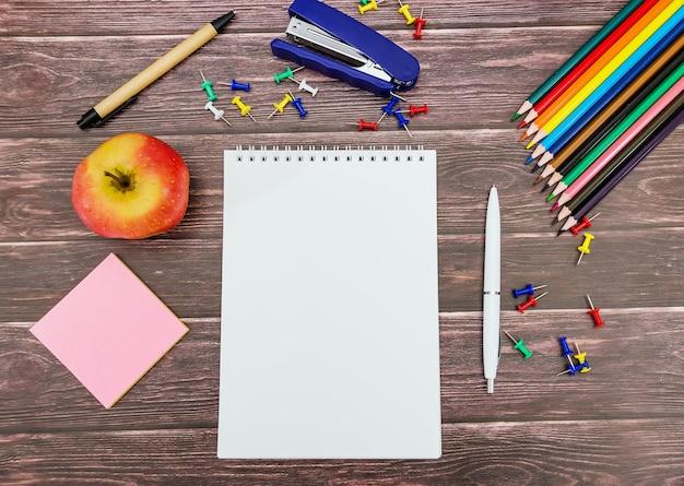 Bloco de notas com uma caneta e material escolar em um fundo de madeira