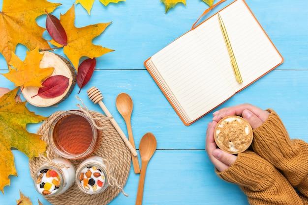 Bloco de notas com uma caneta para escrever na mesa de outono com folhas.