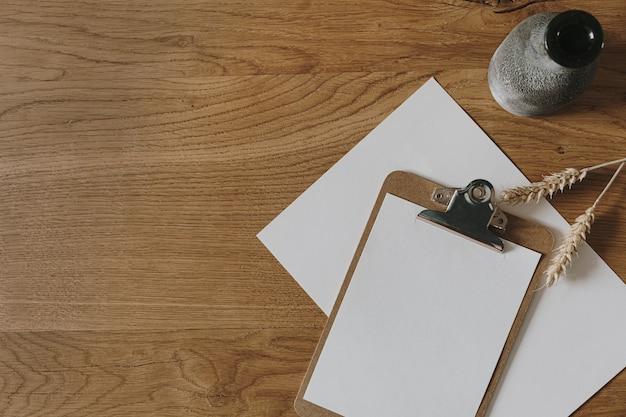 Bloco de notas da prancheta de folha de papel em branco, hastes de centeio de trigo, vaso de madeira. mesa de mesa de espaço de trabalho em casa. camada plana, vista superior.