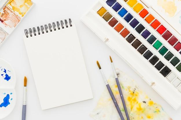 Bloco de notas da vista superior com aquarelas e pincéis