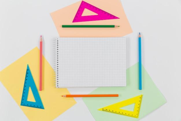 Bloco de notas da vista superior com lápis coloridos em cima da mesa