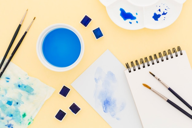 Bloco de notas da vista superior com tintas e pincéis