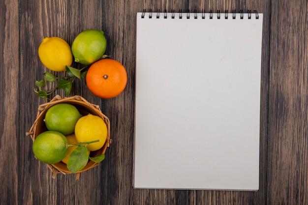 Bloco de notas de cópia da vista superior com limões laranja e limas em uma cesta em um fundo de madeira